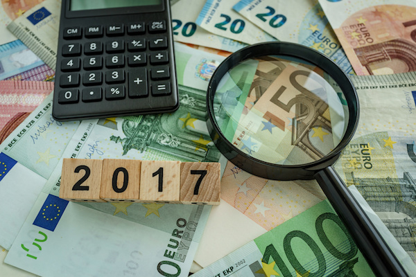 financial tax concept as magnifying glass on pile of euro banknotes, calculator and number 2017 on wooden block.